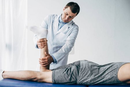 Photo for Physiotherapist stretching leg of patient in hospital - Royalty Free Image