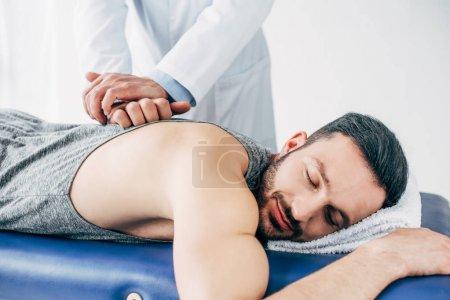 Photo pour Chiropractor massant le dos de l'homme se trouvant sur la table de massage à l'hôpital - image libre de droit