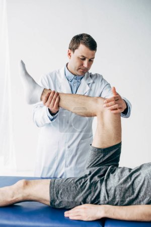 Photo for Handsome Physiotherapist stretching leg of patient in hospital - Royalty Free Image