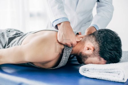 Photo for Chiropractor massaging neck of man lying on Massage Table with towel - Royalty Free Image