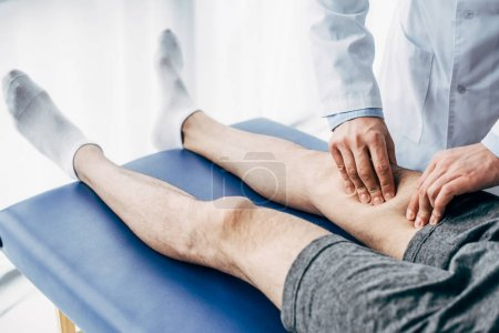 Photo for Partial view of Physiotherapist massaging leg of man on massage table in hospital - Royalty Free Image