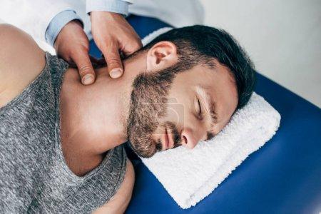 Photo pour Chiropractor massant le cou de l'homme beau se trouvant sur la table de massage - image libre de droit