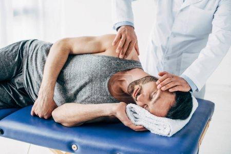 Photo pour Chiropractor massant le cou de l'homme se trouvant sur la table de massage - image libre de droit