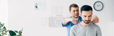 Photo for Panoramic shot of chiropractor massaging neck of handsome man in hospital - Royalty Free Image