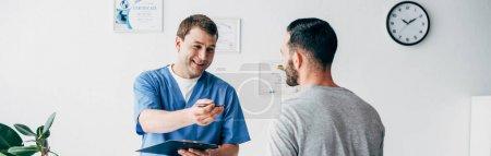 Photo pour Tir panoramique du physiothérapeute de sourire avec le diagnostic près du patient à l'hôpital - image libre de droit
