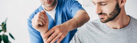 Photo pour Tir panoramique du bras de massage de chiropraticien du patient barbu à l'hôpital - image libre de droit