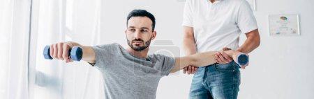 Photo pour Tir panoramique de chiropraticien étirant le bras du beau patient avec des haltères à l'hôpital - image libre de droit