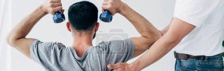 Photo pour Tir panoramique du physiothérapeute aidant le patient avec l'haltère pendant la récupération - image libre de droit