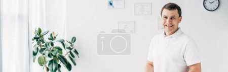 Photo for Panoramic shot of smiling handsome chiropractor in hospital looking at camera - Royalty Free Image