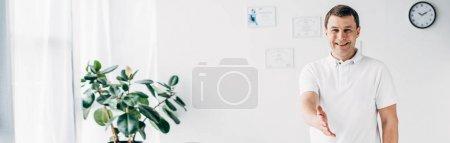Photo pour Plan panoramique de chiropraticien souriant avec la main tendue regardant la caméra à l'hôpital - image libre de droit