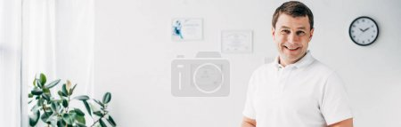 Photo pour Tir panoramique du chiropraticien de sourire dans l'hôpital regardant l'appareil-photo - image libre de droit