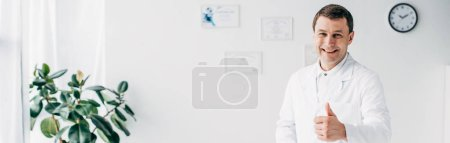 Photo for Panoramic shot of good-looking smiling chiropractor showing thumb up in hospital - Royalty Free Image