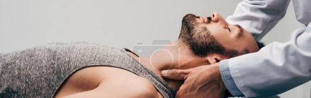 Photo for Panoramic shot of chiropractor massaging neck of man on grey - Royalty Free Image