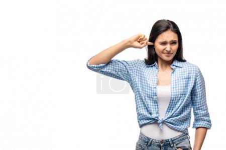 Photo pour Fille insatisfaite branchant l'oreille avec le doigt isolé sur le blanc avec l'espace de copie - image libre de droit