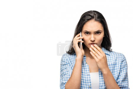 Photo for Shocked girl covering mouth and talking on smartphone Isolated On White - Royalty Free Image