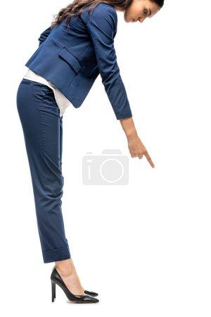 Photo pour Femme d'affaires dans le procès pointant avec le doigt à l'espace de copie isolated on White - image libre de droit