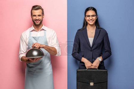 Photo for Happy man in apron with Serving Tray and businesswoman with briefcase on blue and pink - Royalty Free Image