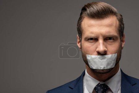 Photo pour Homme d'affaires beau dans le procès avec le ruban adhésif sur la bouche sur le gris avec l'espace de copie - image libre de droit