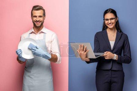 Photo pour Homme dans la plaque de lavage de tablier tandis que la femme d'affaires en utilisant un ordinateur portable sur bleu et rose - image libre de droit