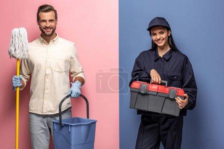Photo pour Homme en gants de caoutchouc avec serpillière et femme en uniforme ouvrier de la construction avec boîte à outils regardant caméra sur bleu et rose - image libre de droit