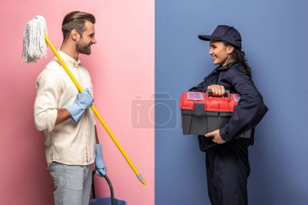 Photo for Man in rubber gloves with mop and woman in construction worker uniform with tool box on blue and pink - Royalty Free Image