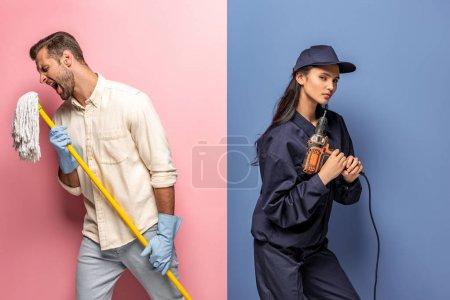 Photo pour Homme dans des gants en caoutchouc chantant avec la vadrouille et la femme dans l'uniforme de travailleur de construction avec la perceuse sur le bleu et le rose - image libre de droit