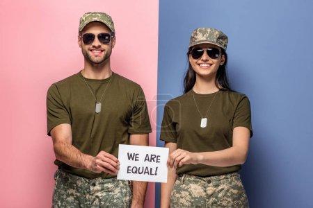 Photo pour Homme et femme heureux dans le papier de fixation d'uniforme militaire avec nous sommes égaux ! lettrage sur le bleu et le rose - image libre de droit