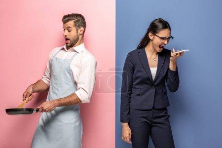 Photo pour Homme confus dans tablier tenant poêle tandis que la femme d'affaires en colère crier sur smartphone sur bleu et rose - image libre de droit