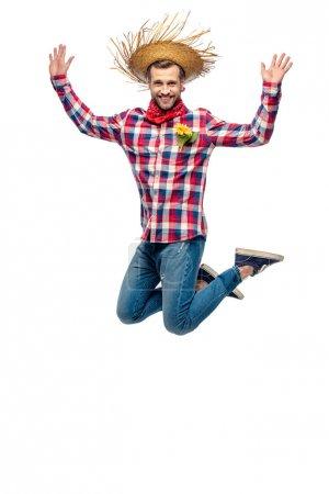 glücklicher Mann mit Strohhut springt mit erhobenen Händen auf weißem Grund