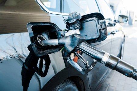 Photo pour Focus sélectif de l'automobile moderne noire de ravitaillement avec de la benzine sur la station-service - image libre de droit