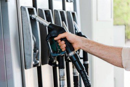 Photo pour Vue recadrée de l'homme tenant la buse de carburant à la station-service - image libre de droit