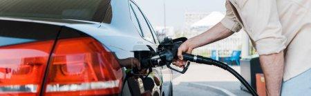 Photo pour Tir panoramique de l'homme retenant la pompe à carburant et faisant le plein voiture noire - image libre de droit