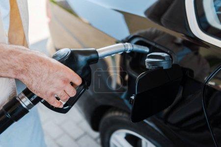 Photo pour Vue recadrée de l'homme tenant la pompe à essence et ravitaillement voiture noire à la station-service - image libre de droit