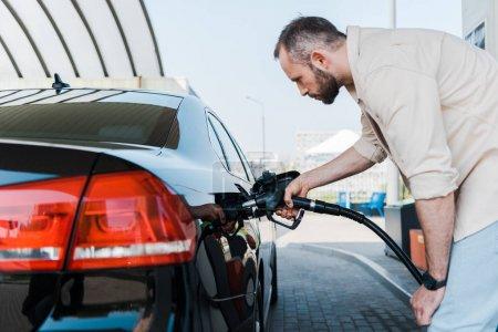Photo pour Homme barbu tenant pompe à essence et de ravitaillement voiture noire à la station-service - image libre de droit