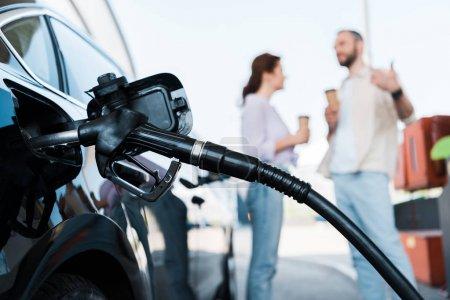 Photo pour Foyer sélectif de ravitaillement automobile noir avec benzine près de l'homme et de la femme sur la station-service - image libre de droit