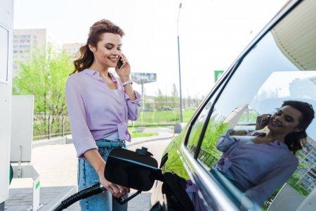 Photo pour Femme heureux retenant la pompe de carburant tout en faisant le plein de voiture avec la benzine et parlant sur le smartphone - image libre de droit