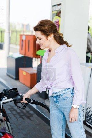 Photo pour Femme heureux retenant la pompe de carburant tout en faisant le plein automobile avec la benzine à la station-service - image libre de droit
