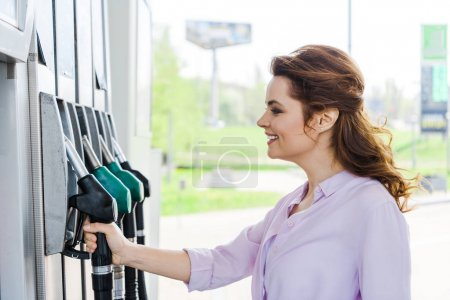 Photo pour Femme heureux retenant la pompe de carburant tout en souriant à la station-service - image libre de droit