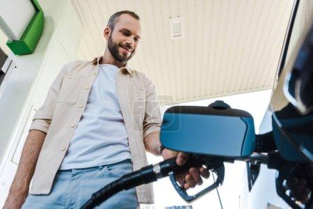 Photo pour Vue à faible angle de l'homme heureux tenant pompe à carburant tout en ravitaillant l'automobile avec benzine à la station-service - image libre de droit