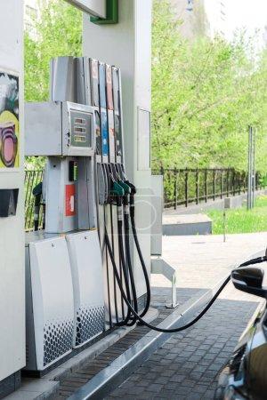 Photo pour L'accent sélectif du ravitaillement automobile avec de la benzine sur la station-service - image libre de droit