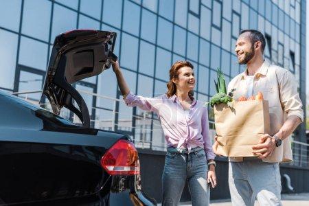 Photo pour Vue basse d'angle de la femme heureuse regardant l'homme avec le sac de papier restant près de la voiture - image libre de droit