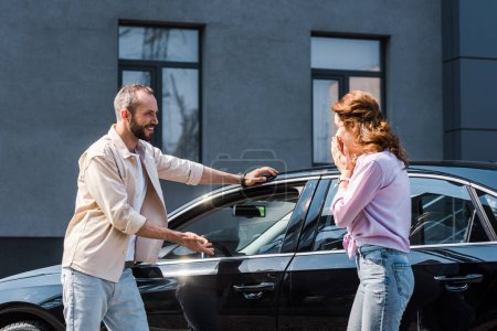 Photo for Cheerful man gesturing near modern car and standing near excited woman - Royalty Free Image