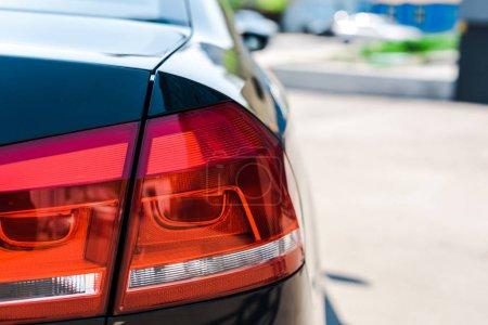 Photo pour Foyer sélectif de feu arrière rouge et brillant de voiture noire et moderne - image libre de droit