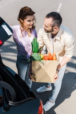 Photo pour Overhead view of happy bearded man putting paper bag in car trunk near attractive woman - image libre de droit