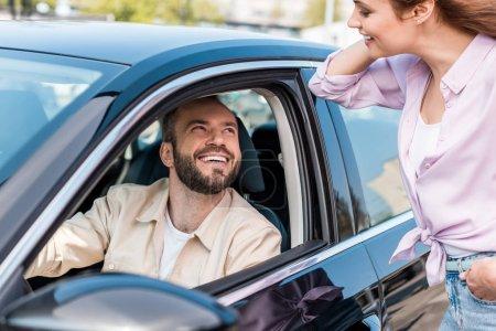 Photo pour Foyer sélectif de femme heureuse debout avec la main dans la poche près de l'homme joyeux dans la voiture - image libre de droit