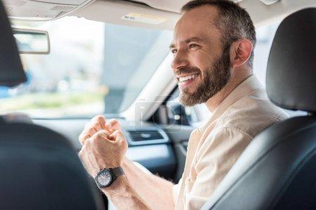 Photo pour Homme gai faisant des gestes tout en souriant et s'asseyant dans la voiture - image libre de droit