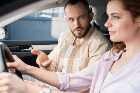 Photo for Selective focus of handsome man gesturing near attractive woman driving car - Royalty Free Image