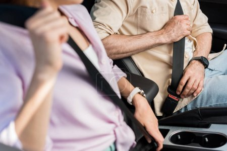 Photo for Cropped view of woman and man fastening seat belts while sitting in car - Royalty Free Image