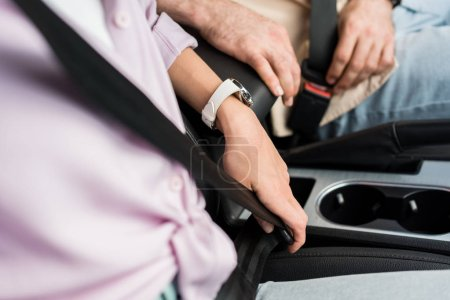 Photo for Selective focus of woman and man fastening seat belts while sitting in car - Royalty Free Image