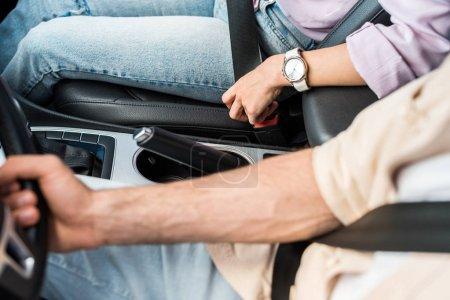 Photo pour Vue au-dessus de la femme attachant la ceinture de sécurité près de l'homme dans la voiture - image libre de droit